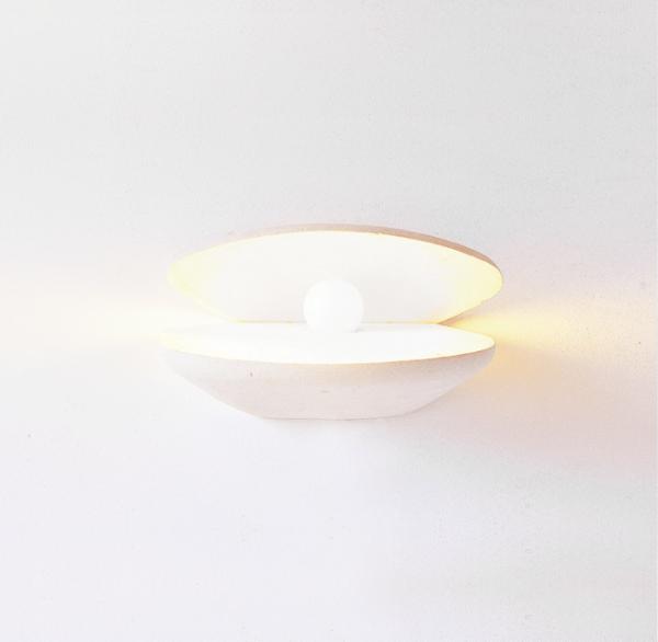 Applique con luce accesa in pietra leccese a forma di perla