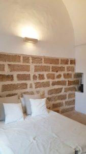 Camera da letto con applique e rivestimenti in pietra leccese